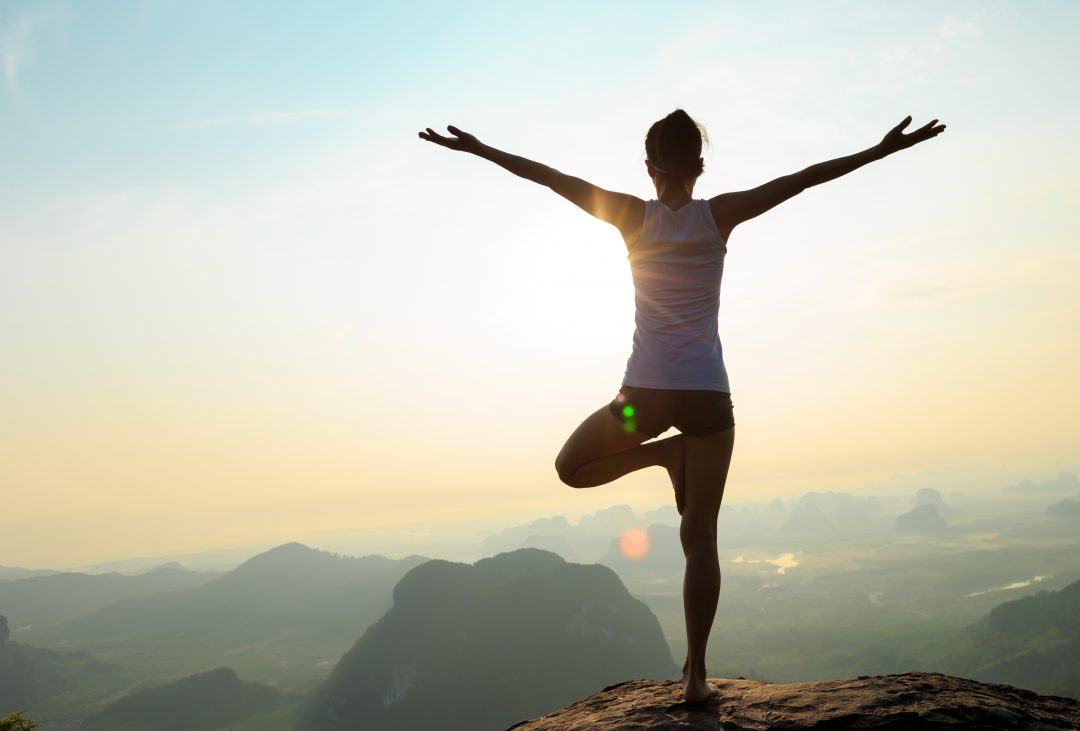 young woman in tree pose on a mountain at sunrise